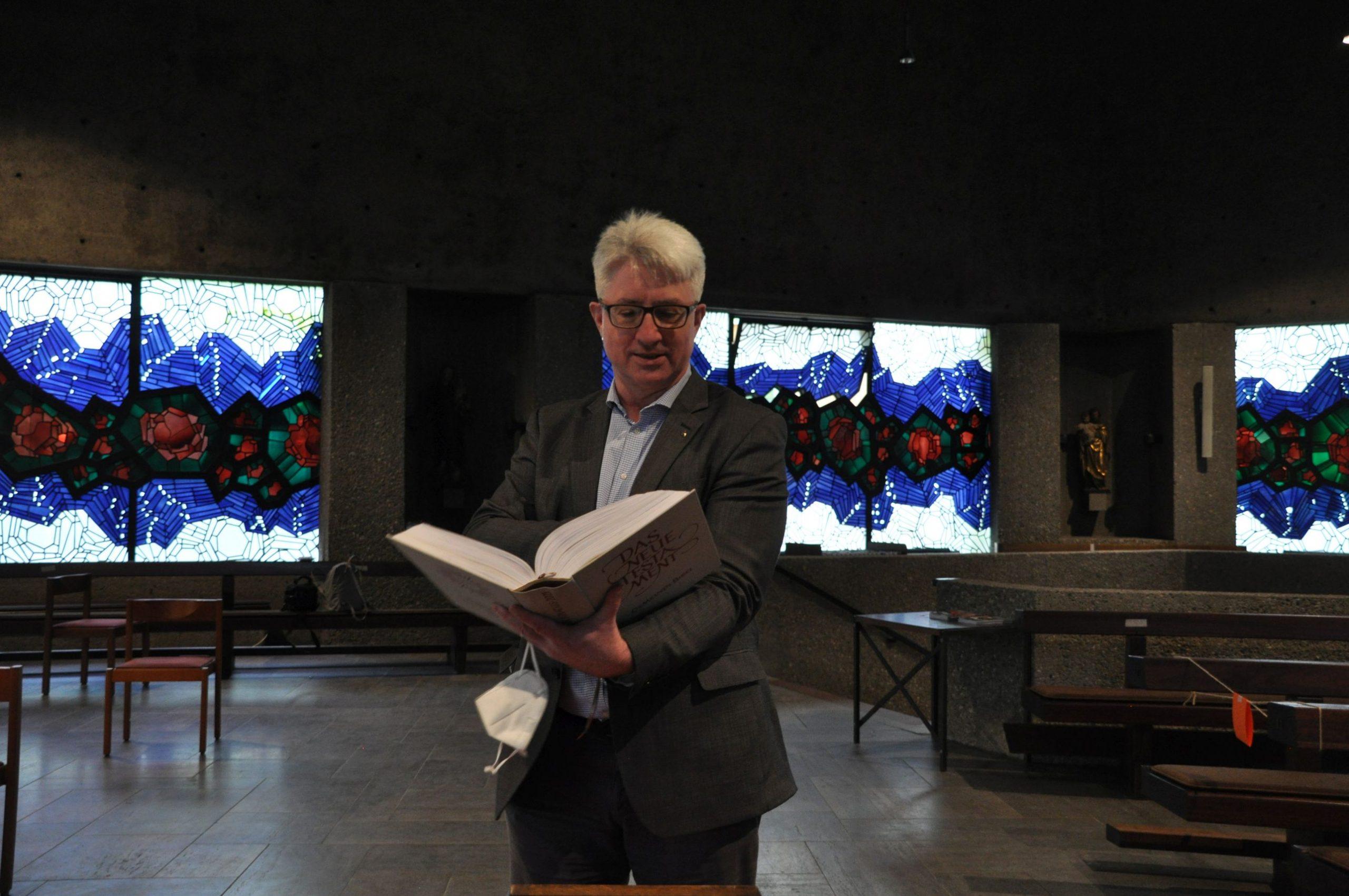 Pater Bernd Günther zeigt die handgeschriebene Bibel.